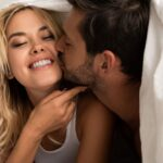 happy husband kissing wife on the bed after good sex